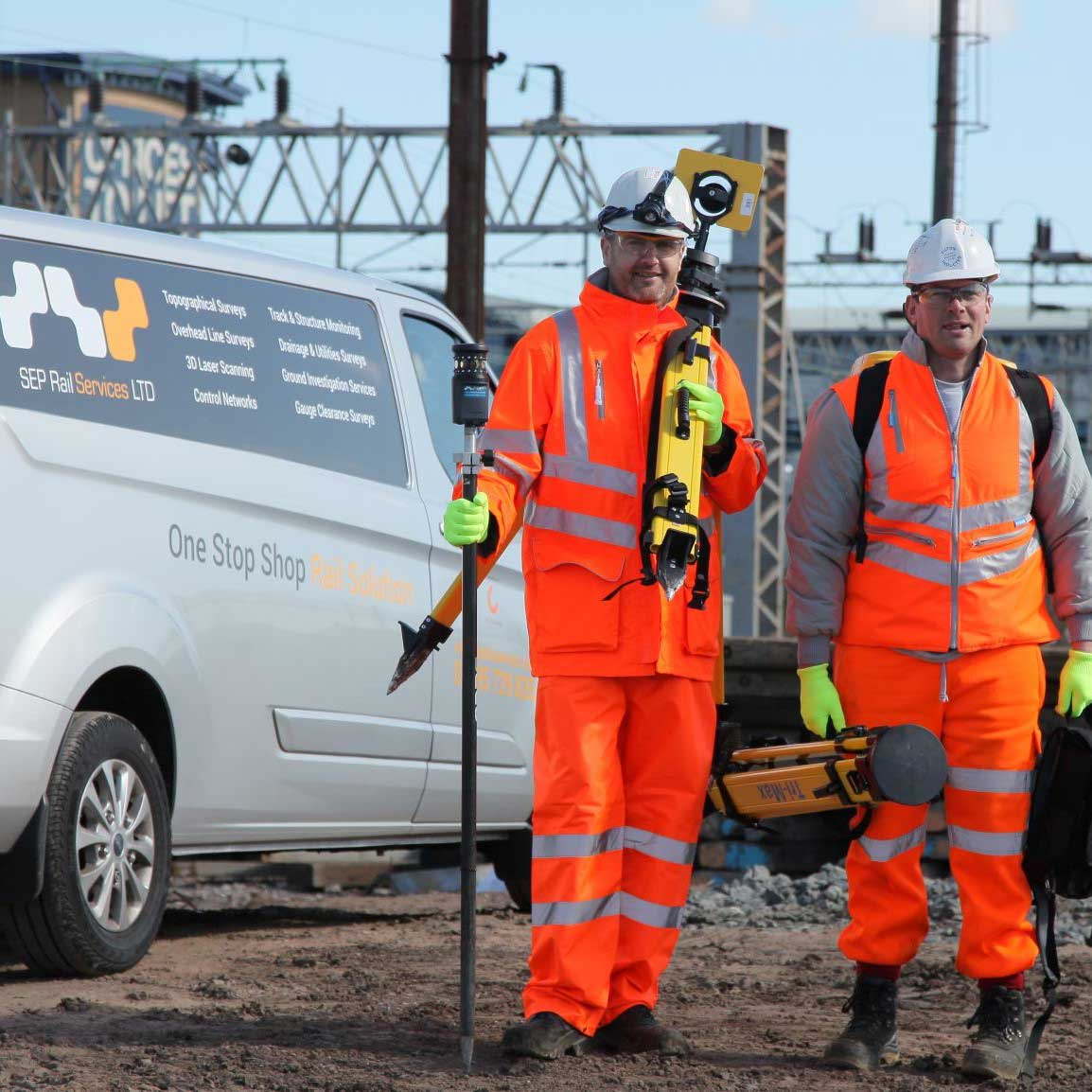 Two workers in orange high visibility clothing holding equipment to fix train rails