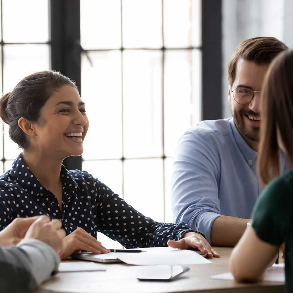 Two woman and a man smiling sat round a desk
