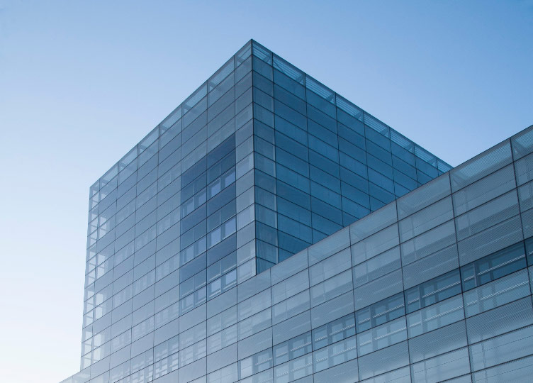View from the ground of the top of a blue glass office building