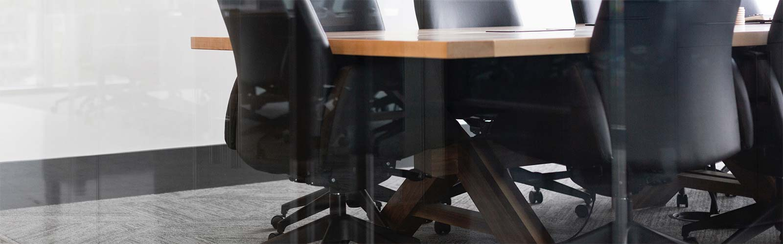 Boardroom desk with black leather chairs surrounding it