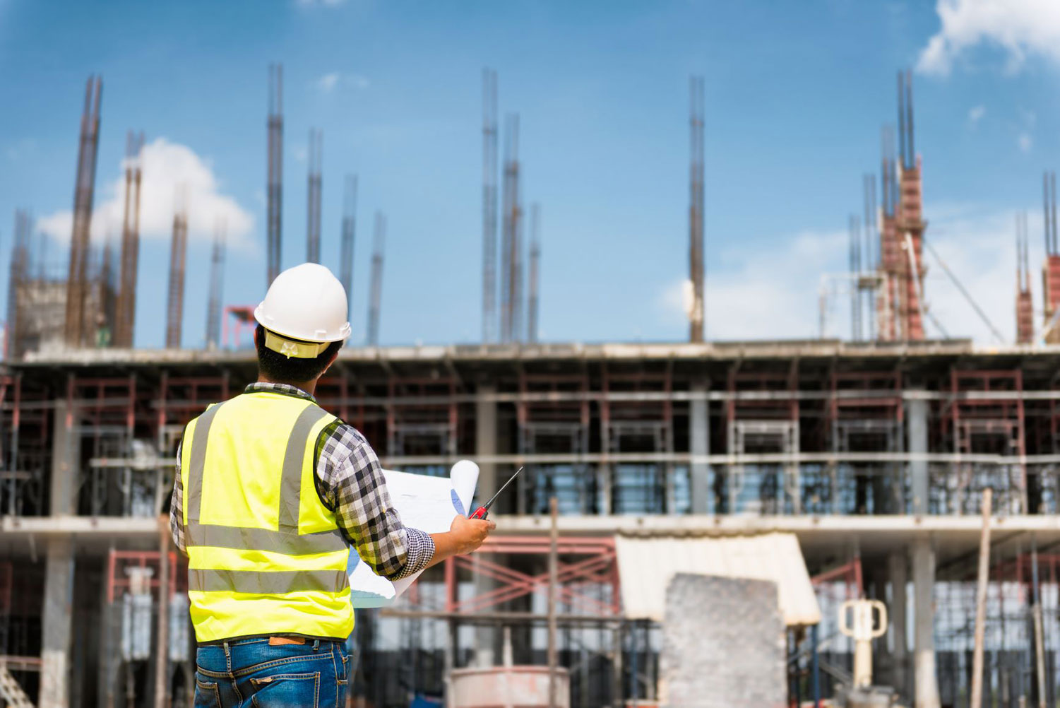 Construction worker holding building plans in front of the building site