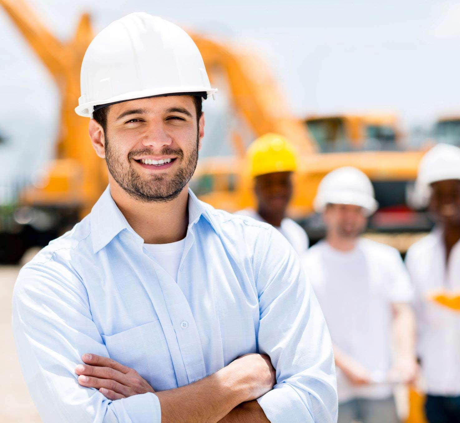 Man in a construction hat and blue shirt stood in front of other construction workers