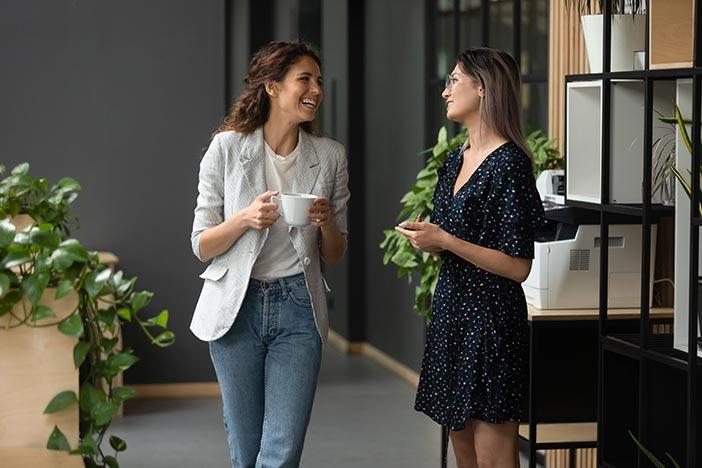 Two women talking in an office walkway