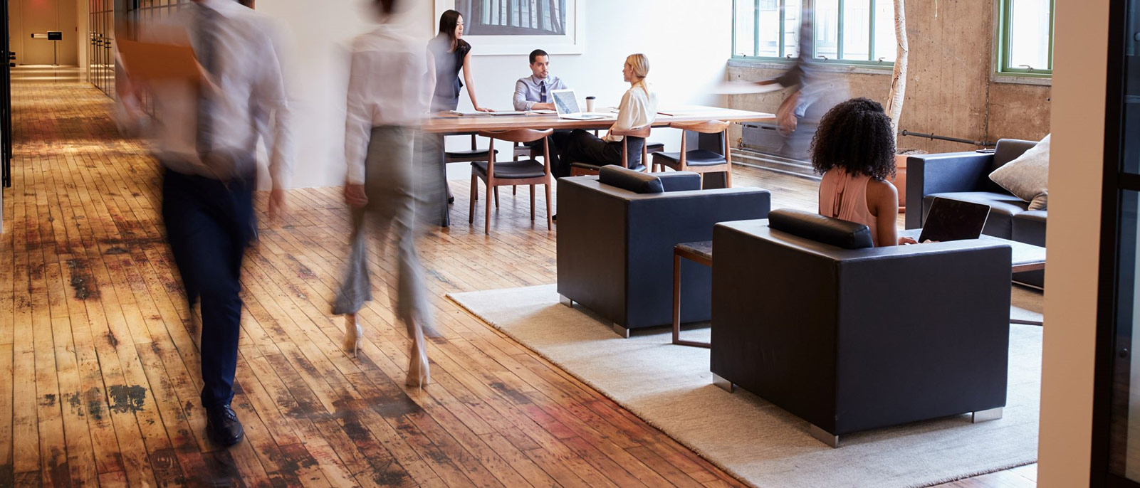 Two people walking through a busy open plan office space