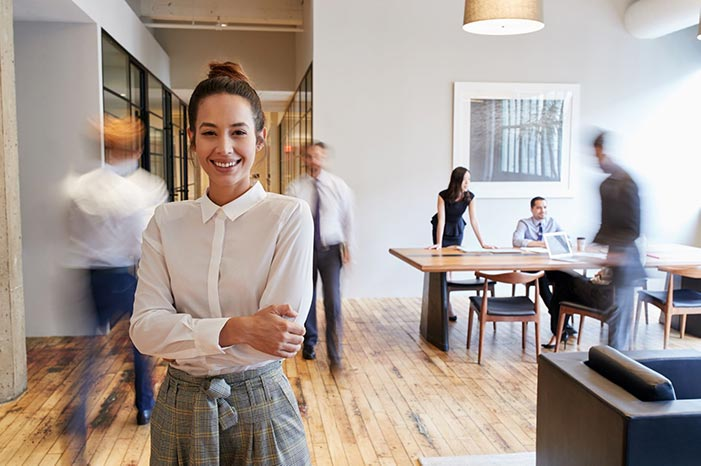 Woman standing smiling in a busy office space as people move around her
