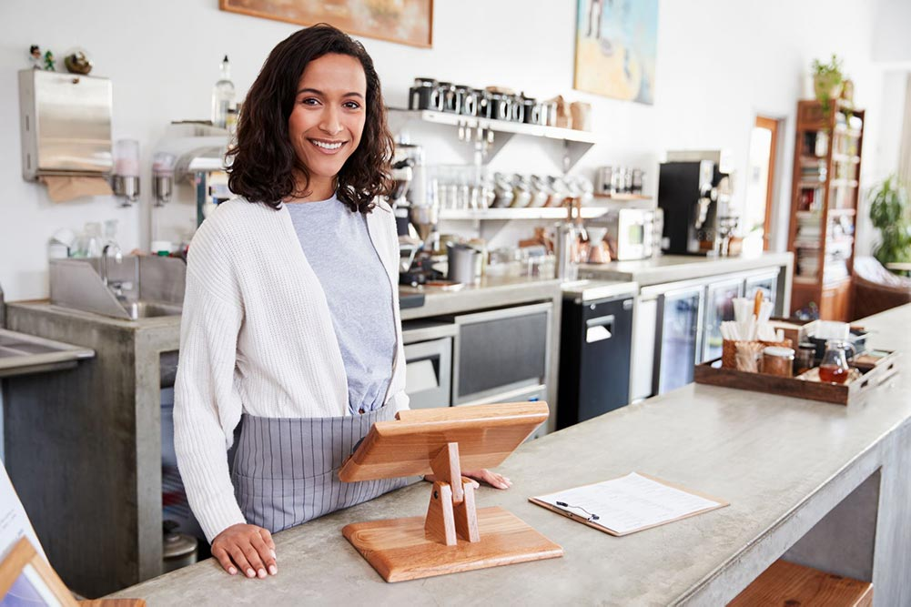 Woman standing at the bar ready to serve at a coffee shop
